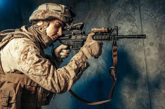 Contratista militar privado estadounidense disparando un rifle. tiro del estudio