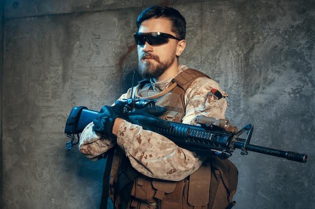 Contratista militar privado estadounidense con rifle. imagen sobre un fondo oscuro