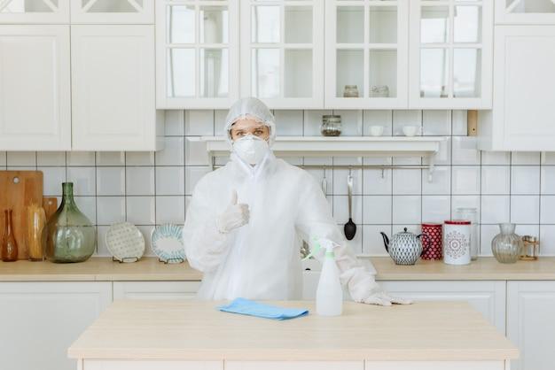 Un contratista profesional de plagas o virus se encuentra en la cocina y muestra un signo positivo