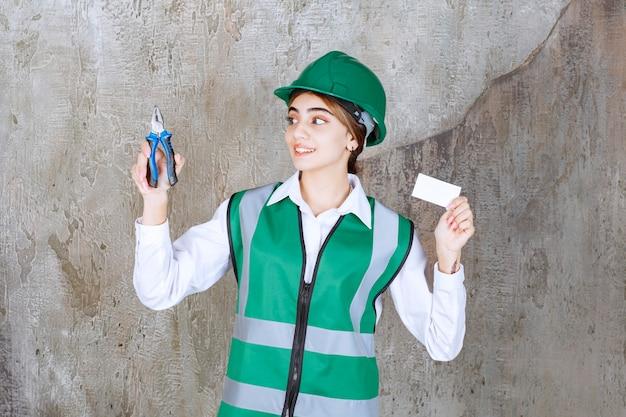 Contratista de sexo femenino en la tarjeta de presentación en su mano sosteniendo pilares para la construcción