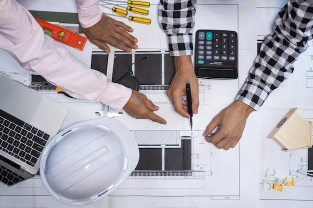 Los contratistas e ingenieros del proyecto consultan el algoritmo de construcción del edificio.