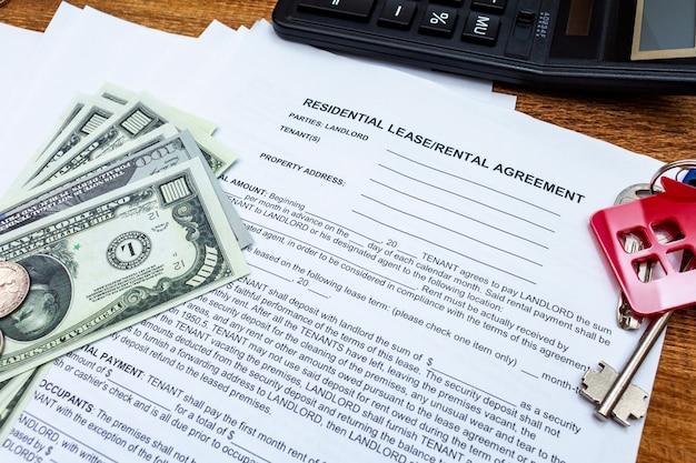 Contrato de alquiler de casa, hogar, propiedad, arrendamiento inmobiliario con monedas de dinero, llaves.
