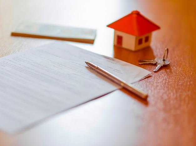 Contrato de arrendamiento / alquiler documento con llaves y pluma. texto destacado