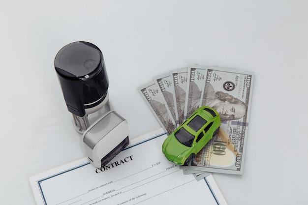 Contrato de compra de un coche con billetes de dólar, sellos y llaves del coche sobre un fondo blanco.