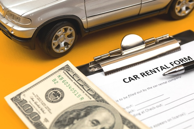 Contrato de documento de alquiler de coche. foto de concepto de servicio de alquiler de coches. escritorio con coche de juguete, portapapeles, dinero y bolígrafo.