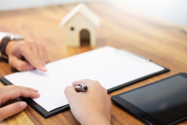 Contrato de firma del cliente, términos acordados y solicitud aprobada y análisis de préstamo hipotecario de valoración, reunión con el trabajador bancario o agente de bienes raíces.