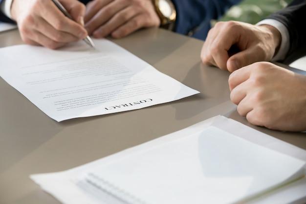 Contrato de firma del hombre de negocios en la reunión, foco en el documento, clos