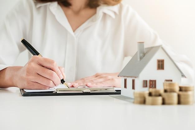 Contrato de firma de la mujer de negocios para comprar la casa.