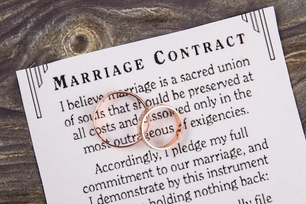 Contrato de matrimonio y anillos de boda. papel de primer plano con texto y primer plano de dos anillos.