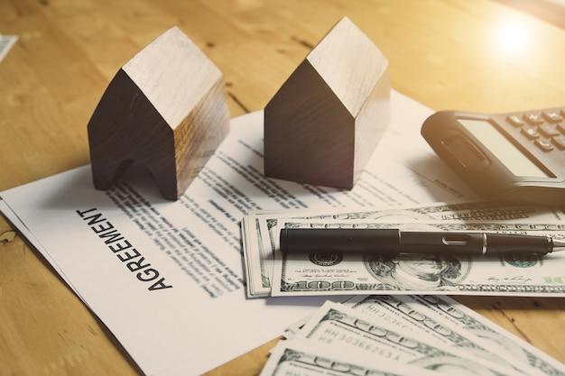 Contrato de papel para firmar acuerdo comprar casa con dinero y calculadora. efecto del relleno del vintage.