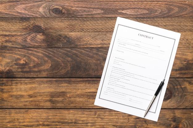 Contrato de plano y pluma sobre mesa de madera.