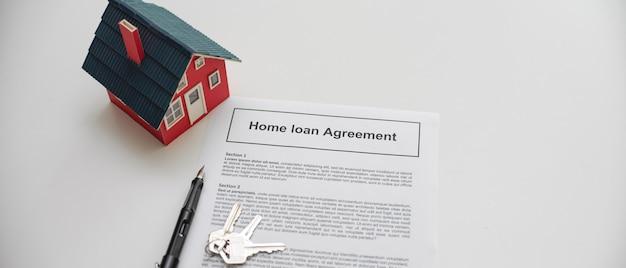 Contrato de préstamo hipotecario con bolígrafo, modelo de casa y llave de la casa en la mesa blanca