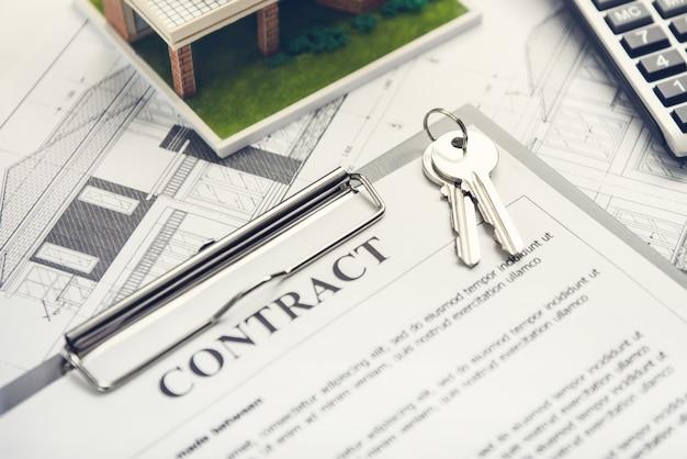 Un contrato de préstamo hipotecario con las llaves de la casa y el plano de planta preparado para un nuevo propietario
