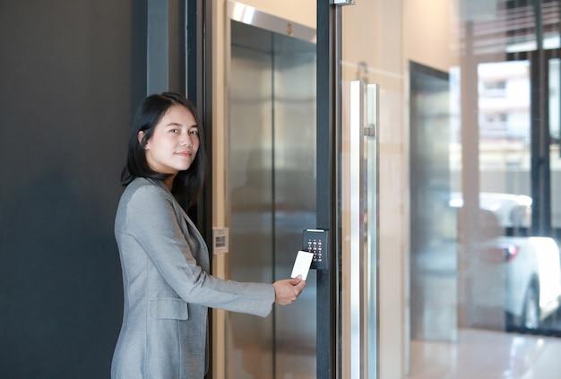 Control de acceso a la puerta: mujer joven oficial que sostiene una tarjeta de acceso para bloquear y desbloquear la puerta de acceso.