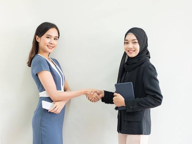 Control de mano de dos mujeres con una sonrisa en la tableta musulmana del asimiento de la mano del hijab un vestido en el teléfono elegante del asimiento de la mano del traje moderno, concepto del negocio del éxito.