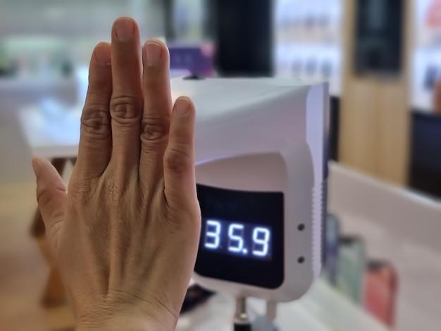 Control de la temperatura corporal de la mano femenina con termómetro infrarrojo digital con sus manos