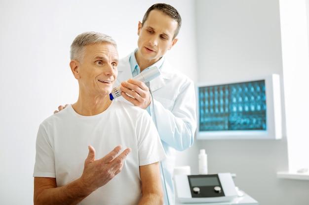 Control de ultrasonido. doctor guapo e inteligente de pie detrás de su paciente y usando un dispositivo de escaneo especial mientras realiza un chequeo