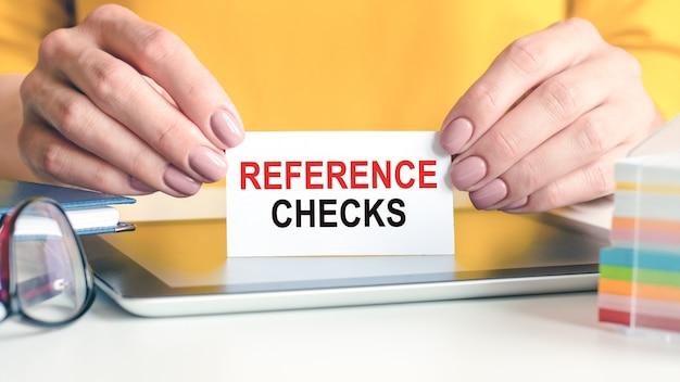 Los controles de referencia se escriben en una tarjeta de presentación blanca en manos de una mujer. fondo amarillo. vasos, tableta y bloque con papel multicolor para notas. se puede utilizar para negocios, concepto publicitario.