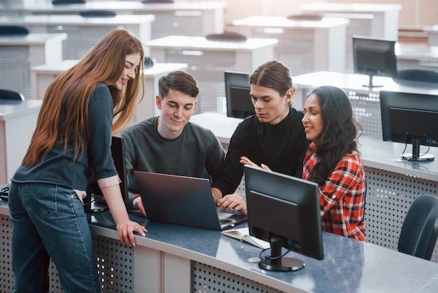 Conversación activa. grupo de jóvenes en ropa casual que trabajan en la oficina moderna