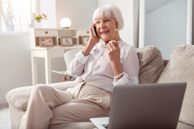 Conversación agradable. alegre anciana sentada en el sofá de la sala de estar y hablando por teléfono mientras sonríe alegremente