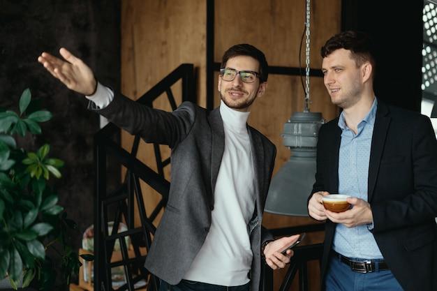 Conversación de hombres de negocios, señalando con la mano a la ventana
