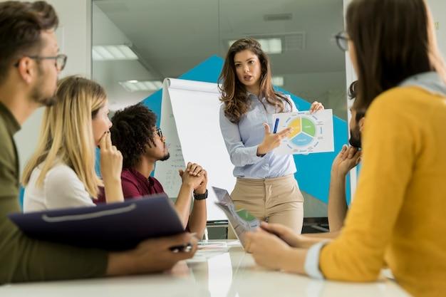 Conversación entre trabajadores jóvenes en una pequeña empresa de nueva creación con una carta de papel.