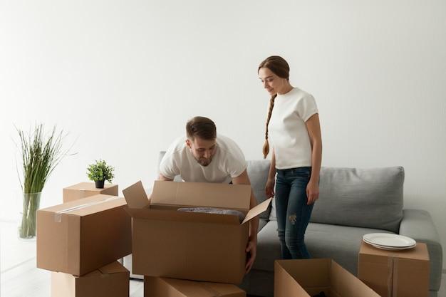Cónyuges jóvenes cargando cajas que se mudan a piso nuevo.
