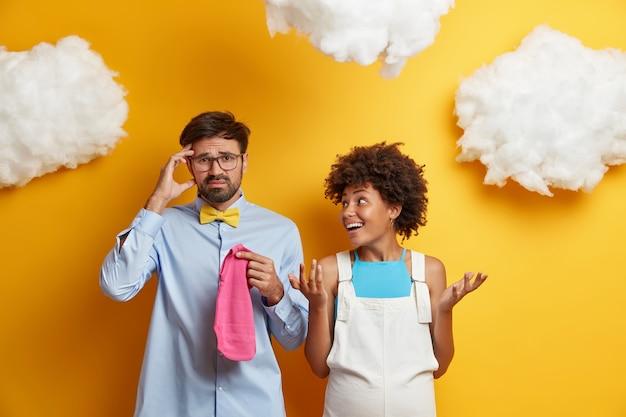 Los cónyuges recién casados se preparan para el nacimiento de un hijo, compran ropa infantil, se paran desconcertados y vacilantes contra el amarillo. esperando padres en casa. concepto de familia y embarazo.