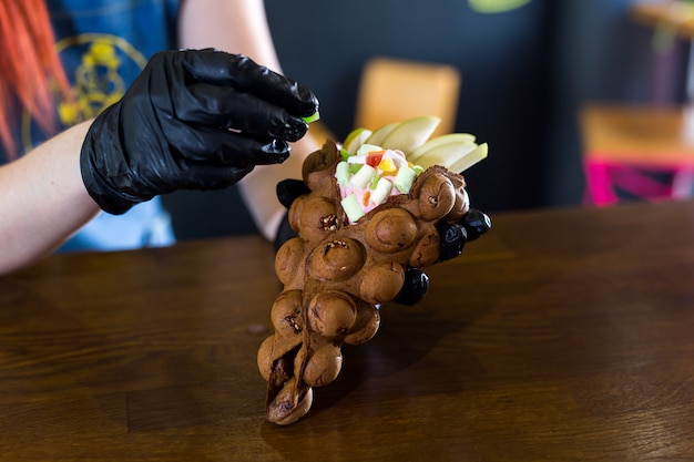 Cook prepara gofres de hong kong con helado, mermelada y fruta. mujer joven con obleas de burbuja de hong kong