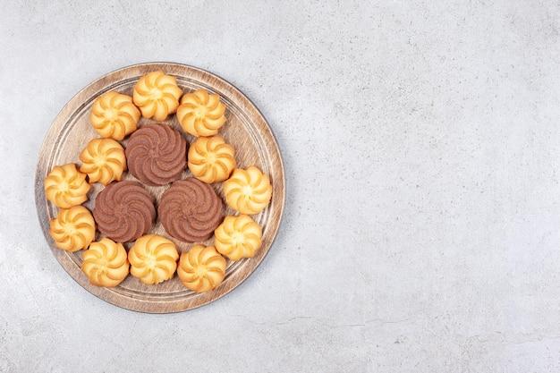 Cookies decorativamente alineadas sobre tabla de madera sobre fondo de mármol.