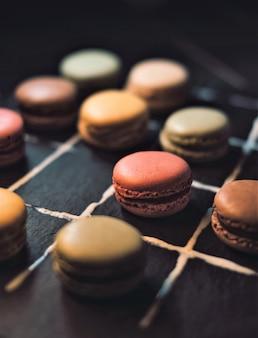 Cookies de varios colores sobre una superficie oscura.