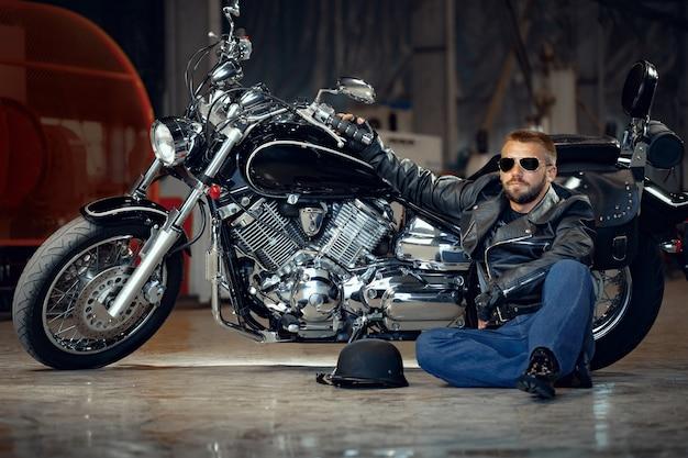 Cool biker hombre con gafas de sol sentado cerca de su moto