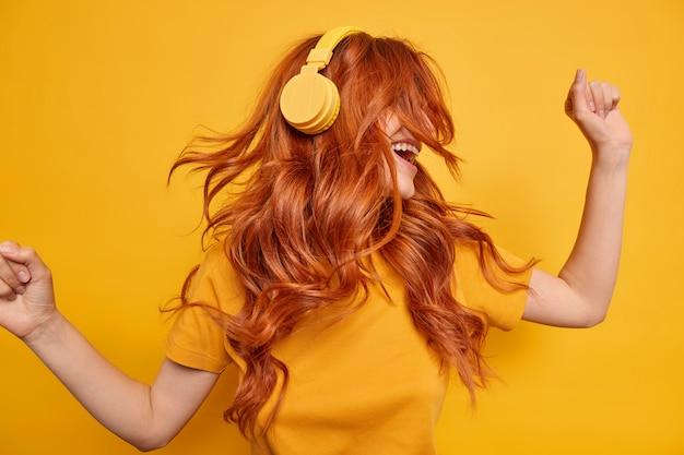 Cool chica milenaria mantiene los brazos levantados baila despreocupada disfruta cada pedazo de música usa audífonos inalámbricos en las orejas tiene cabello rojo flotando en el viento vestida con una camiseta casual