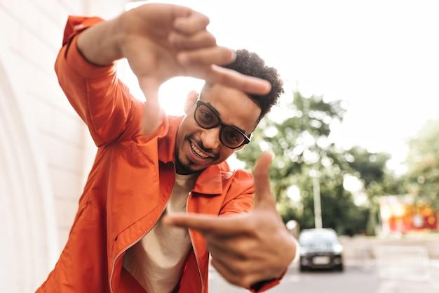Cool emocionado rizado hombre de piel oscura con chaqueta naranja brillante y gafas de sol sonríe y hace que la cámara firme con sus dedos afuera