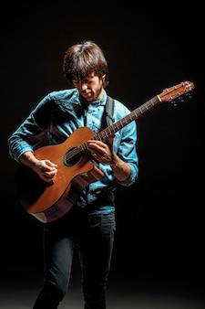 Cool guy parado con guitarra en la pared oscura