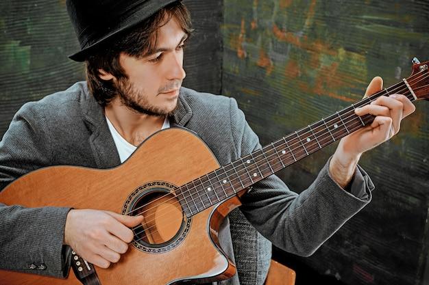 Cool guy con sombrero tocando la guitarra en el espacio gris