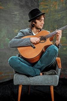 Cool guy con sombrero tocando la guitarra en gris