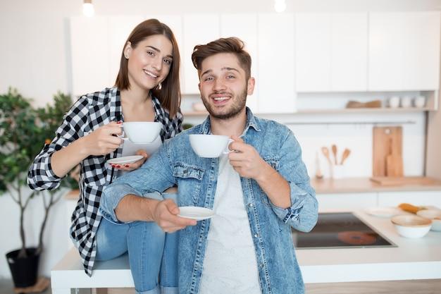 Cool hipster joven feliz y mujer en la cocina, desayuno, pareja juntos en la mañana, sonriendo, tomando té