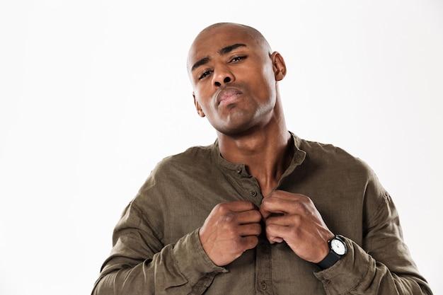 Cool hombre africano mostrando se abrocha la camisa y mirando