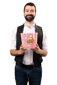 Cool hombre comiendo popcorns sobre fondo blanco aislado