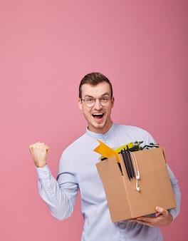 Cool hombre feliz con una caja de cartón con bolígrafos, plantas y cosas diferentes