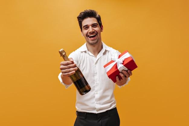 Cool joven emocional con camisa blanca y pantalón negro se regocija, sostiene una caja de regalo roja y una botella de champán en la pared naranja.