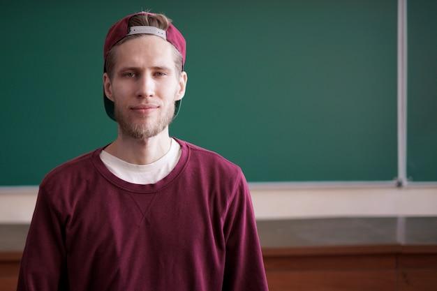 Cool joven estudiante inconformista en gorra snapback y casual en la universidad con pizarra en el fondo