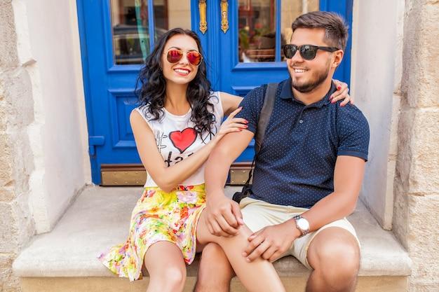 Cool joven hermosa pareja hipster enamorada sentada en la calle de la ciudad vieja