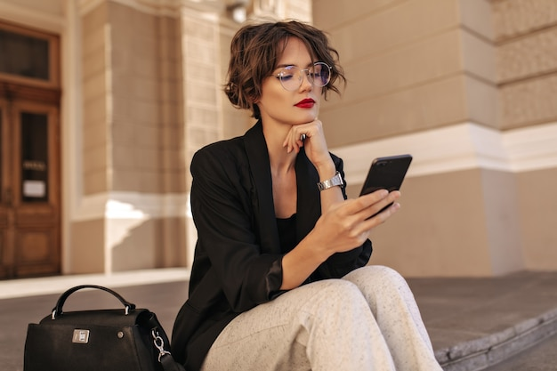 Cool mujer con cabello ondulado en pantalones blancos y chaqueta negra con teléfono afuera. mujer elegante en eyeyglases sentado al aire libre.