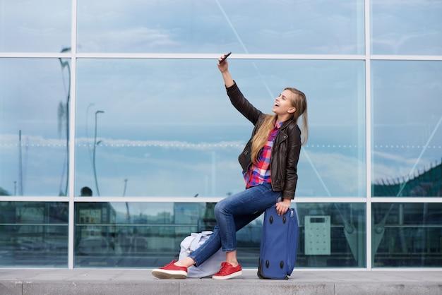 Cool mujer joven tomando selfie con bolsas de viaje