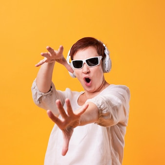 Cool senior mujer escuchando música y bailando