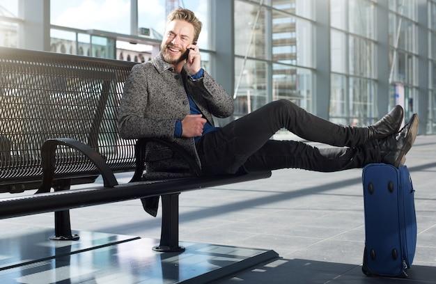 Cool travel man relajante en el aeropuerto con teléfono móvil