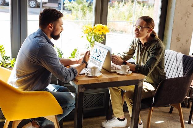 Cooperacion placentera. hombres jóvenes inteligentes sentados en sus computadoras portátiles mientras trabajan juntos en su proyecto