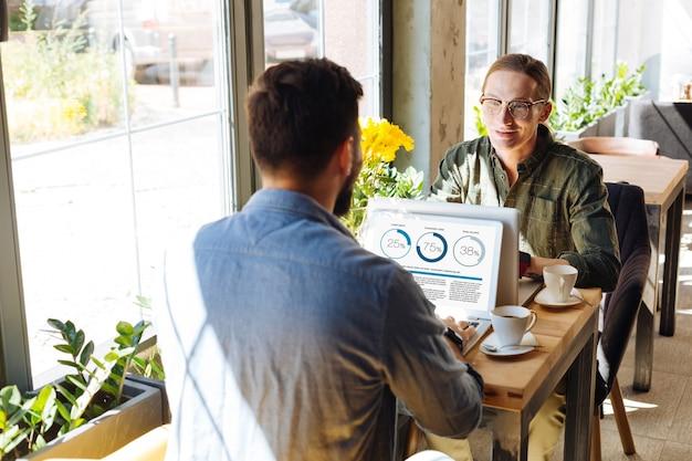 Cooperacion placentera. hombres positivos agradables sentados con sus computadoras portátiles mientras discuten su proyecto de trabajo